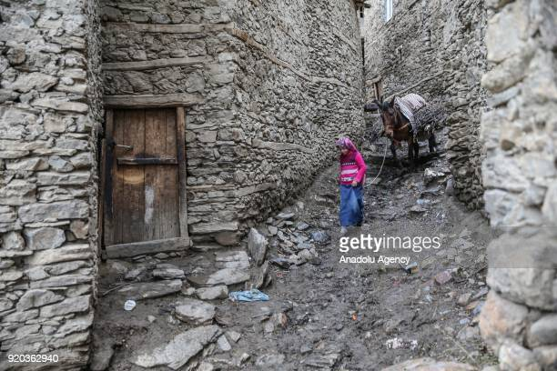 A kid walks with a donkey around the stone houses at her village in Hizan district in the southeastern province of Bitlis Turkey on February 18 2018...