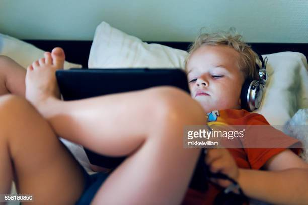 kid watches a streaming movie on his digital tablet before bedtime - mood stream stock pictures, royalty-free photos & images