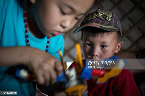 A kid watches as his sister assembles a robot toy inside their yurt near the small village of Lün in Töv Province Mongolia