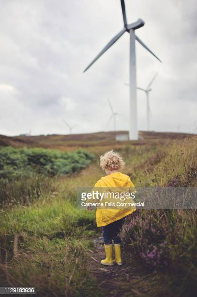 kid watching wind turbine - windmill stock pictures, royalty-free photos & images