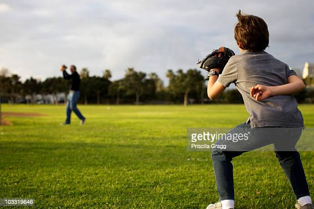 A kid wearing a baseball glove waits for his dad to throw the ball at the park.