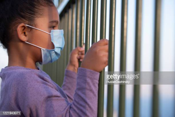 a kid wearing a face mask, looking away through the fence rods. coronavirus pandemic concept. - child behind bars stock pictures, royalty-free photos & images