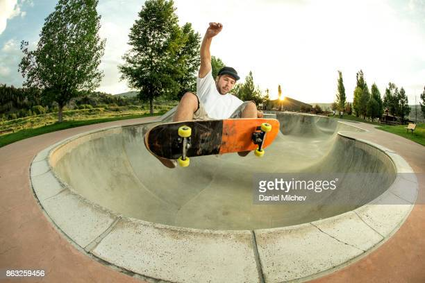 kid with a snowboard jumping out of a skate park bowl. - skating stock pictures, royalty-free photos & images
