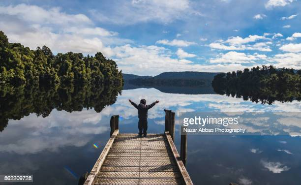 Kid with arms outstretched at Lake Mapourika.