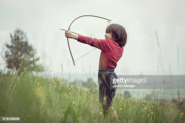 Kid with bow and arrow on meadow