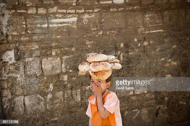 kid with bread on her head - egypt stock pictures, royalty-free photos & images