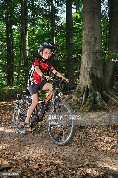 Kid with helmet on a bike in the woods