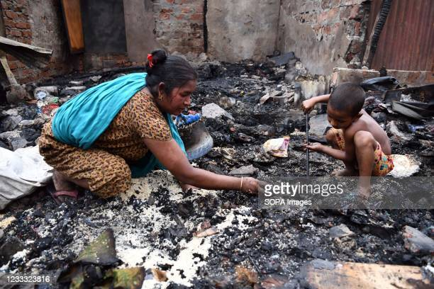 Kid with his mother search for reusable materials after a fire swept through the slum. Several hundreds of houses were gutted as the devastating fire...