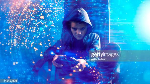 kid with hooded shirt plays video game and holds game controller in his hands - gamer stock pictures, royalty-free photos & images