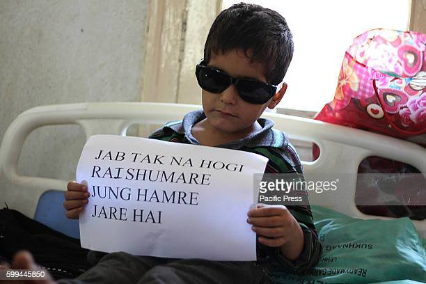 A kid with pellet injuries in his left eye holds a placard as a mark of protest in a hospital in Srinagar the summer capital of Indian controlled...