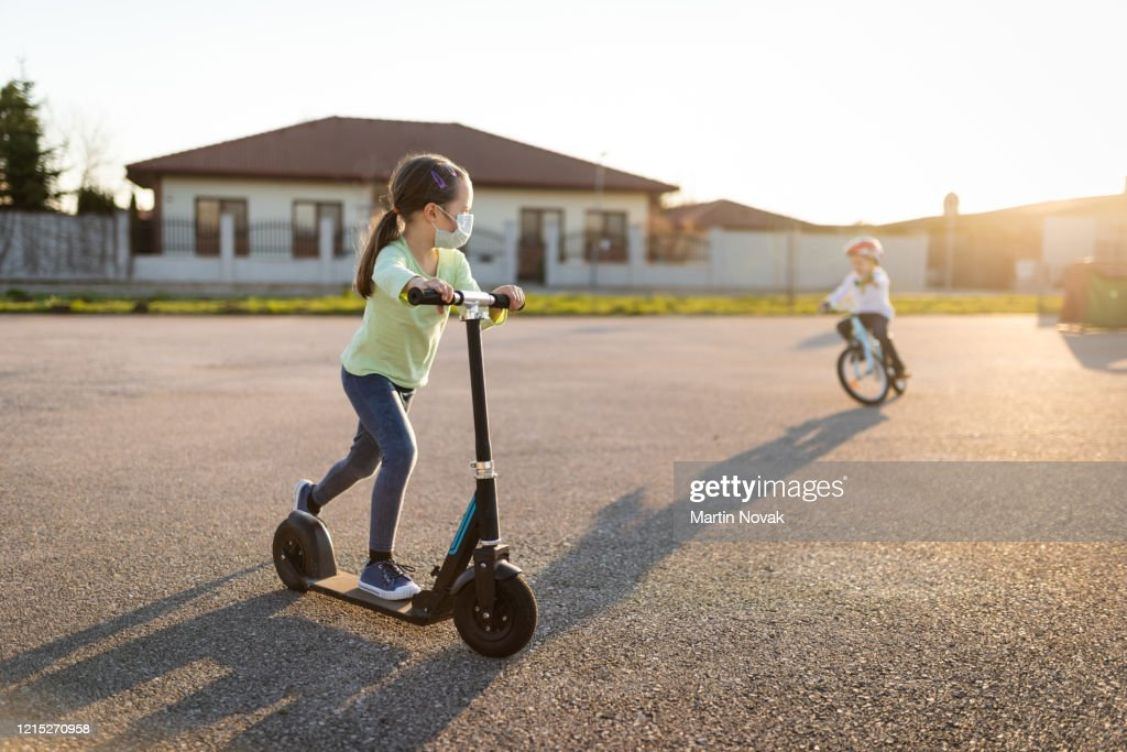 Kid with protective face mask riding on kisck scooter : Stock Photo