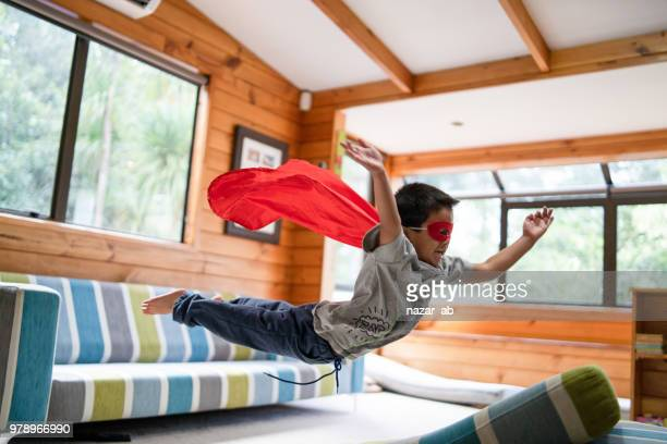 kid with superhero mask jumping on sofa. - mid air stock pictures, royalty-free photos & images