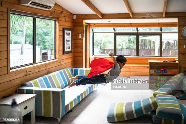 kid with superhero mask jumping on sofa. - home insurance stock pictures, royalty-free photos & images