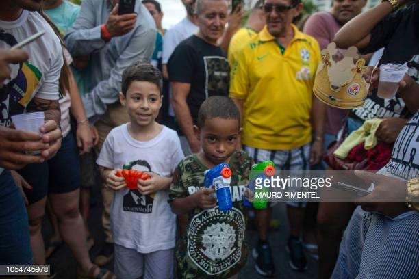 A kid with two water toy guns wears a shirt with the name of the farright presidential candidate for the Social Liberal Party Jair Bolsonaro in a...