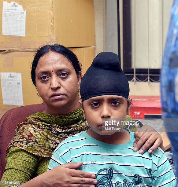 A kidnapped boy rescued by Delhi police with his mother at Delhi Police head quarters in New Delhi on Sunday