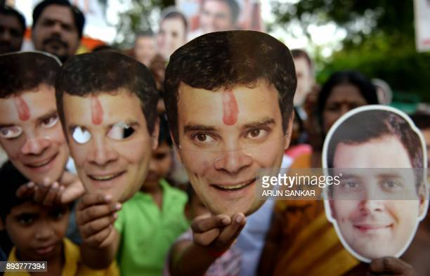 Kids along with members of the Indian National Congress party celebrate as they display masks of the newlyelected party President Rahul Gandhi in...