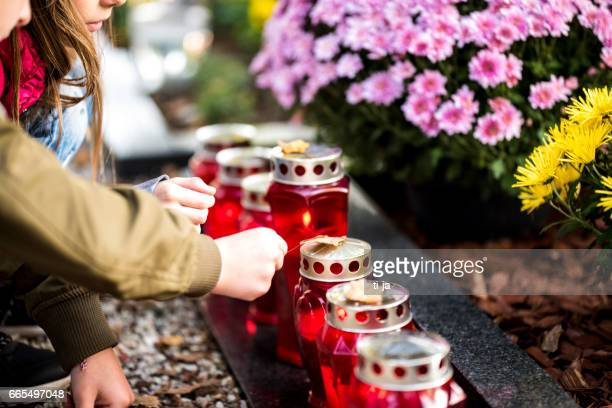 kids and candles by the grave - funeral stock pictures, royalty-free photos & images