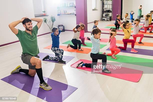 Enfants et coach de faire des exercices d'étirement sur sports training.