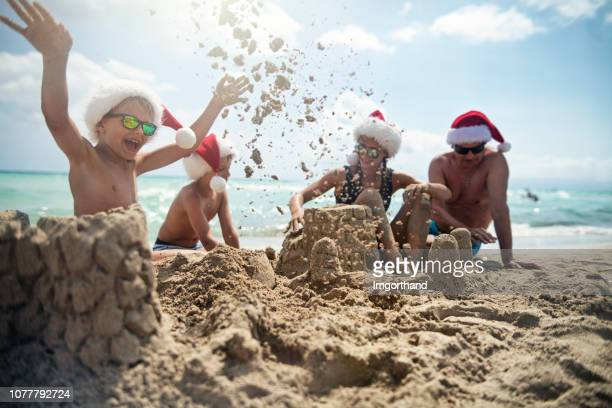 kids and grandfather having fun building sandcastles - beach christmas stock pictures, royalty-free photos & images