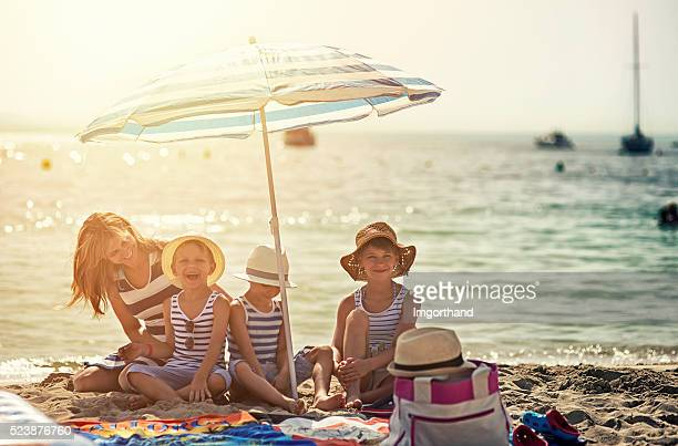 Kids and mother enjoying summer vacation on the beach