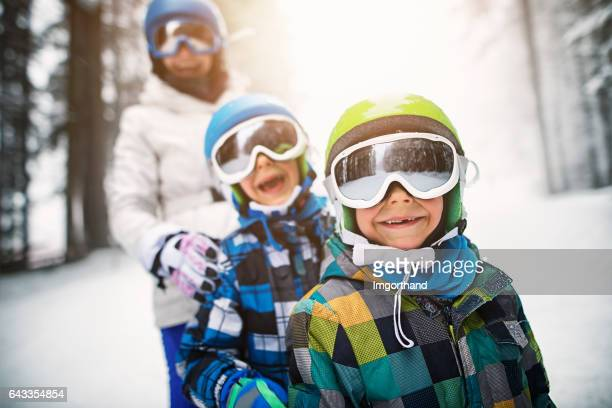 Kids and mother having fun skiing together on winter day