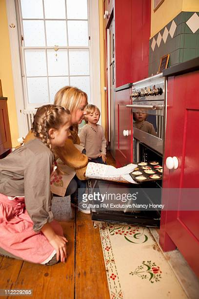 Kids and mother putting cakes in oven