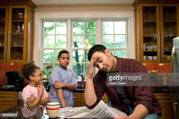 Kids annoying father at kitchen table