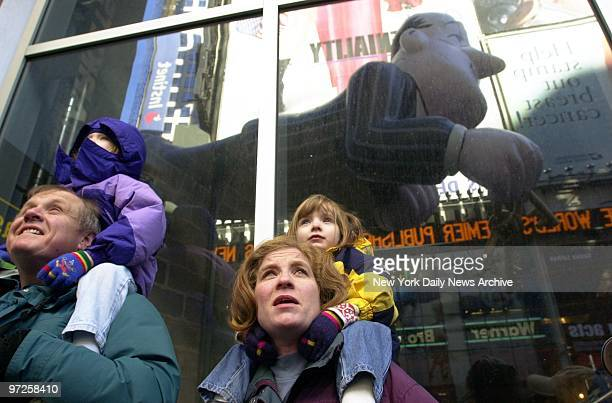Kids are propped up on their parents' shoulders to watch the balloons and floats as they pass through Times Square during the 74th annual Macy's...