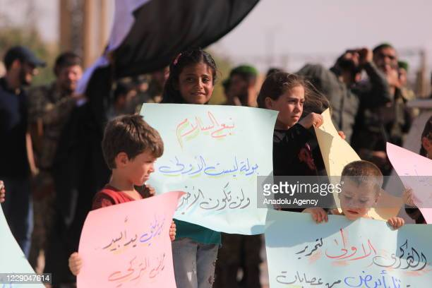 Kids are seen in front of the members of Syrian National Army as they attend an event to mark the first year of Operation Peace Spring as life turned...