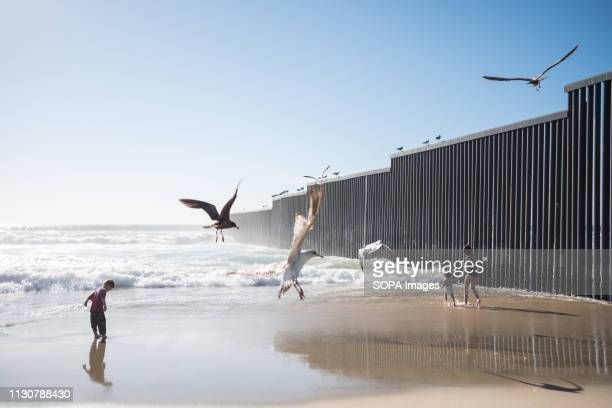 Kids are seen playing near the dividing border wall between the United States and Mexico where many asylum seekers have crossed. In February 2019,...