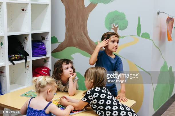 kids at a table in a school while two look toward their left - calabasas stock pictures, royalty-free photos & images
