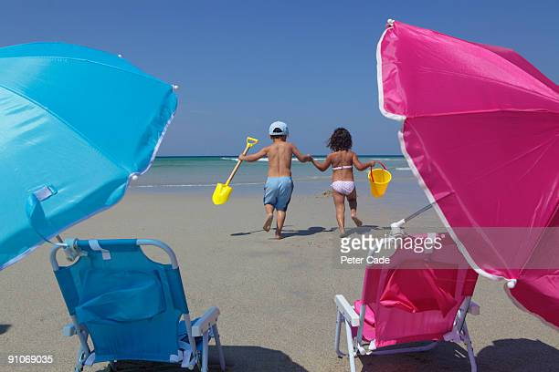 kids at beach with chairs, bucket and spade