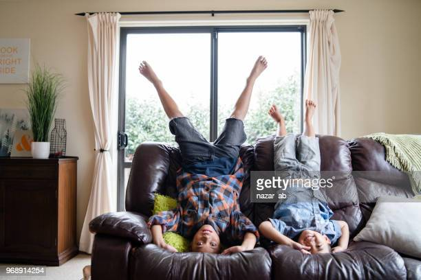 kids at home having fun being upside down on sofa in living room. - polynesian culture stock photos and pictures