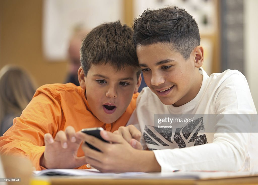 Kids at school using smartphone : Stock Photo