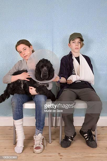 kids at vet, dog lying on lap