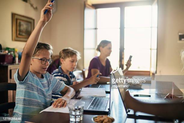 kids attending remotely to video conference class at school. - hand raised stock pictures, royalty-free photos & images
