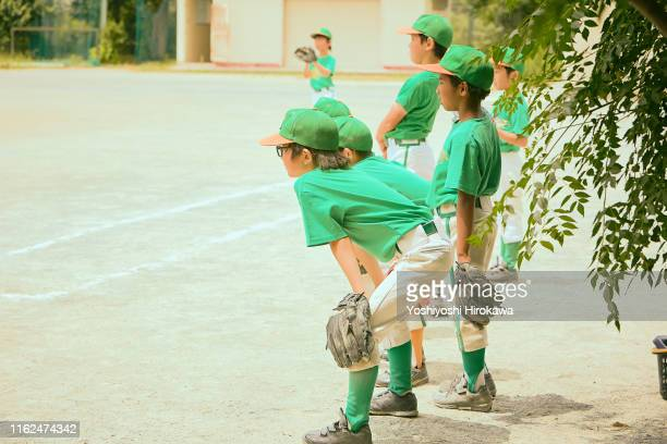 kids(6-9) baseball friend looking at teammates on field - 野球帽 ストックフォトと画像