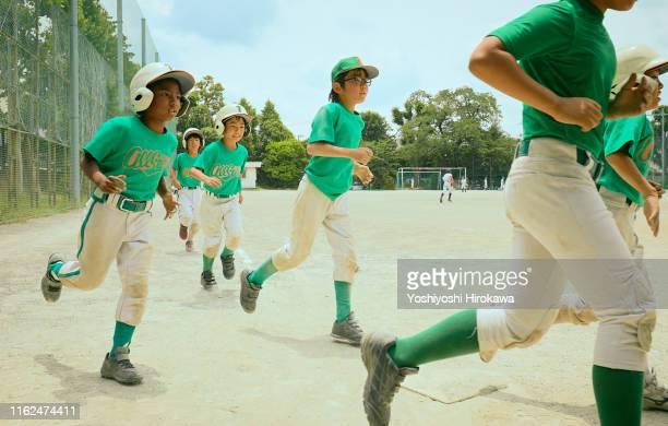 kids baseball player running on field - honkbal teamsport stockfoto's en -beelden