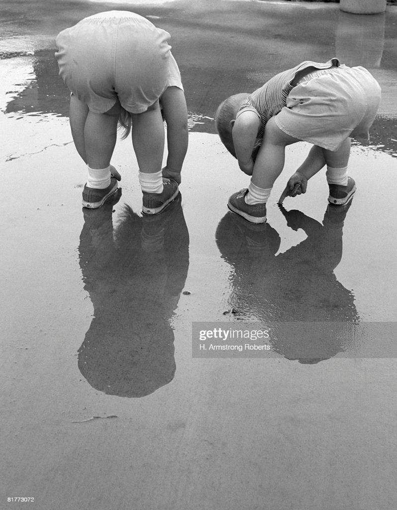 2 Kids Bending Over Rear View Backs To Camera Playing In Mud Puddle Rain Reflection In Water. : Stock Photo