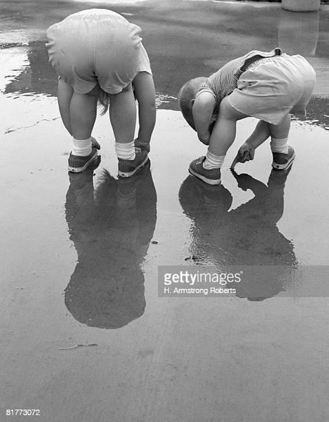 2 kids bending over rear view backs to camera playing in mud puddle rain reflection in water. - girls fanny stock photos and pictures
