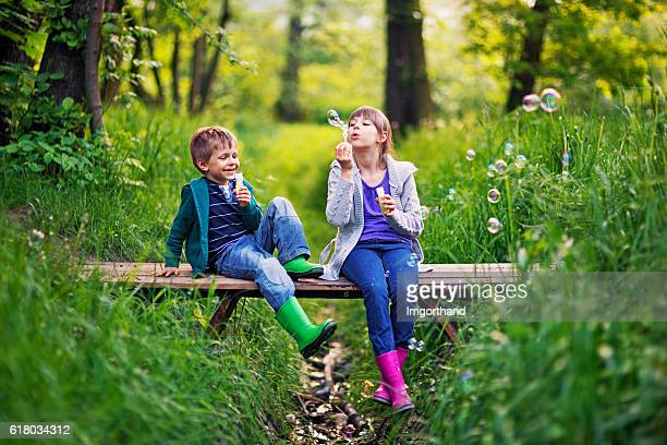 kids blowing  bubbles on the bridge - spring flowing water stock pictures, royalty-free photos & images