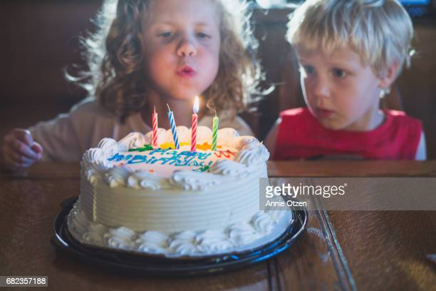 Kids Blowing Out Candles on Cake