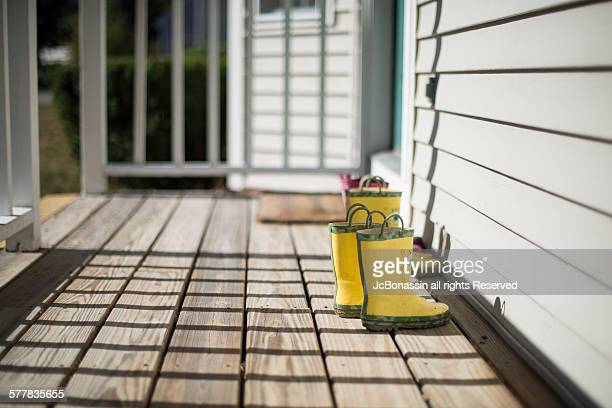 kids boots on the porch - jcbonassin stock pictures, royalty-free photos & images
