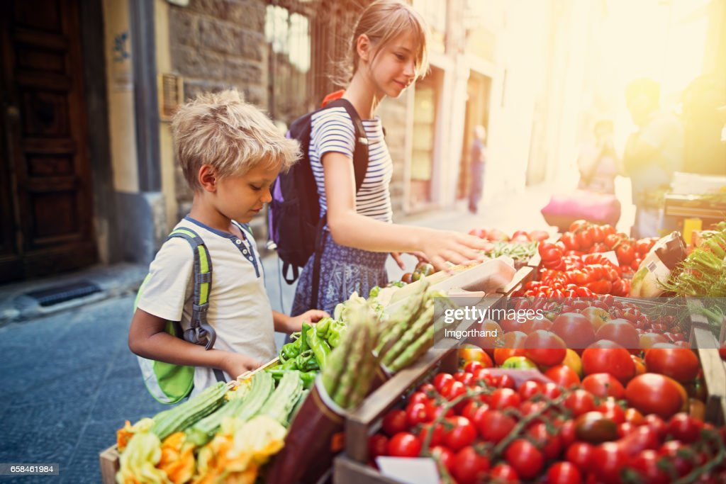 Kids browsing vegetables at Florence street stand : Stock Photo