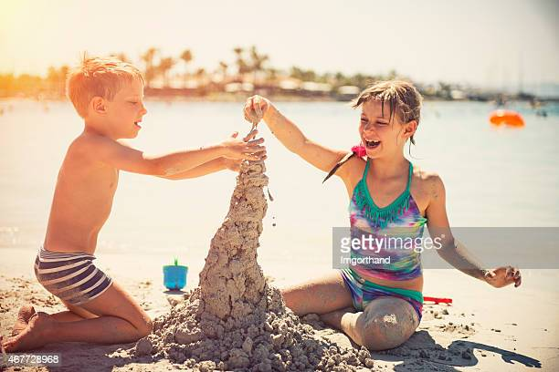 Kids building a sandcastle on a sunny beach