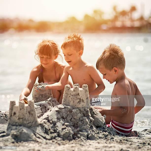 Kids building a sandcastle on beautiful beach