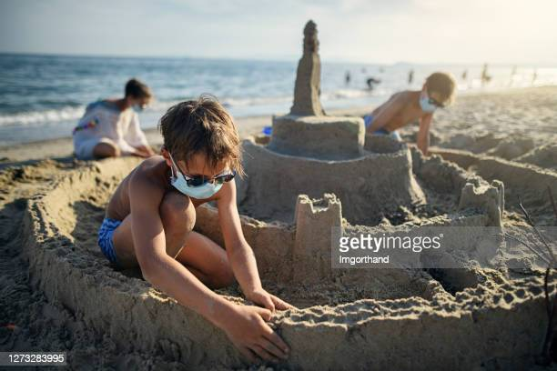 kids building sandcastle on beach during covid-19 - outdoor pursuit stock pictures, royalty-free photos & images