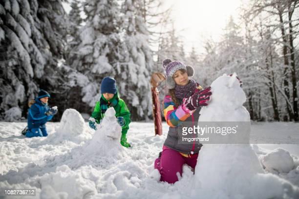enfants de construire des bonhommes de neige sur une journée d'hiver - bonhomme de neige photos et images de collection