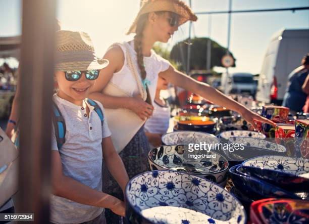 kids buying souvenirs on flea market in andalusia, spain - ceramic stock photos and pictures