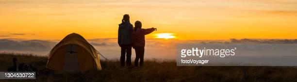 bambini accampati su un'idilliaca cima di montagna con vista sul panorama del tramonto dorato - image foto e immagini stock